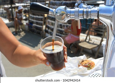 City of Kurgan, Russia, July 28, 2011: The pouring kvass is foaming in a mug. A woman's hand and a cock.