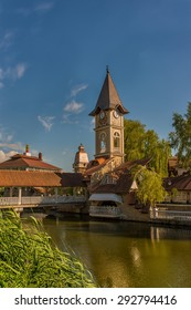 City landscape in Chernivtsi. Lake in the park. View of the clock tower.