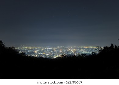 City landscape at night sky with many stars, long exposure astronomical photograph
