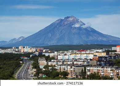 City landscape of Petropavlovsk-Kamchatsky City: urban development, residential buildings on background of beautiful active Koryak Volcano on sunny day. Kamchatka Peninsula, Russian Far East, Eurasia.