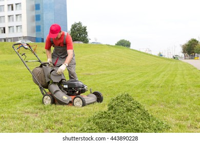City landscaper worker man stop mower machine and unloading grass from lawn cutter bag