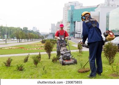 City landscapers gardeners mowing lawn with gas trimmer and lawnmower machine