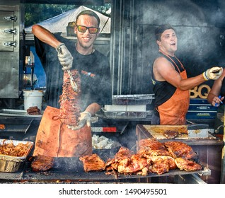 City of Langley downtown, BC, Canada. 2019 August 17. Ribfest in the City. Cooking Ribs on the grill, massive, two young Caucasian men, professional cooks, delicious sauce.