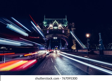City light trails of red London bus traffic on Tower Bridge in London at night