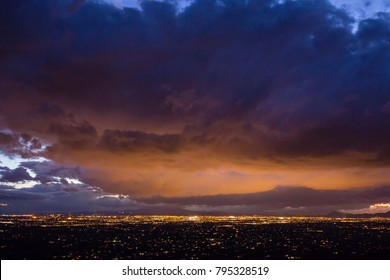 City lights illuminate the bottom of dense clouds over Tucson, Arizona.