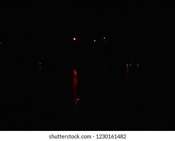 City lights at night, seen directly and reflected in river water