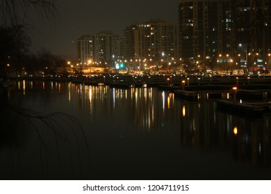 City lights reflected in water, condominium towers above marina in modern waterfront city