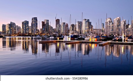 City lights reflection in calm water at sunset. False Creek and Yaletown. View from Kitsilano seawall. Vancouver. British Columbia. Canada.