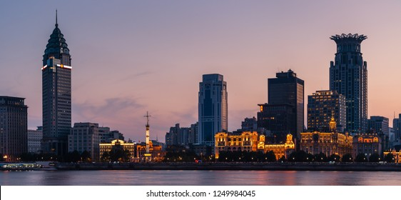 The city lights of Shanghai come alive along the Bund as evening settles in over the city.