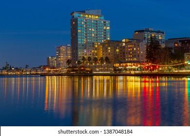 City lights turn on after the sun set over Lake Merritt