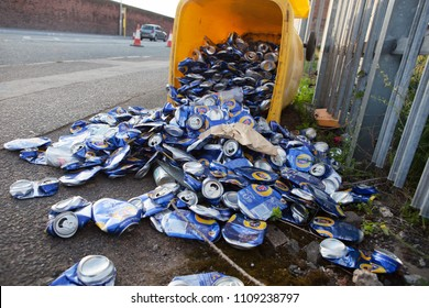 City of Liverpool, Great Britain, 05.28.2018 Yellow recycle box with hundreds of beer cans scattered on the street. Environment conservation and littering concept