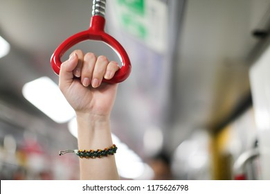 City living concept female hand holding a looped handle in urban public transportation (local subway, underground or sky train) with blurred background of stanchions, hanging straps and ceiling lights