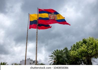 The city of Loja flag flies beside the Flag of Ecuador against a cloudy sky