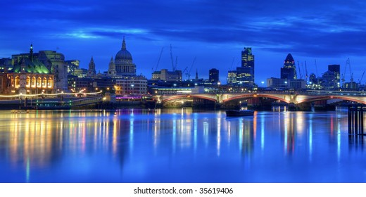 The City of London at Dawn. The lights of the city buildings are reflected in the still waters of the River Thames