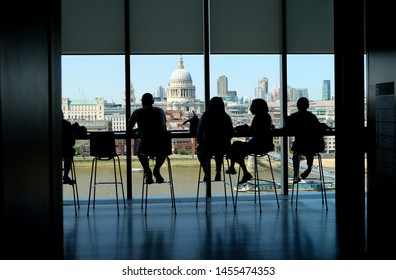 City of London, United Kingdom 6th July 2019: London skyline including St pauls cathedral, view from cafe at Tate on south bank, river Thames in foreground, silhouettes of people on chairs enjoying view