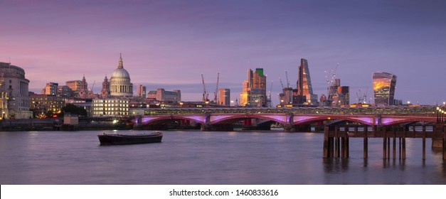City of London, United Kingdom 6th July 2017: London skyline panorama seen from south bank, river Thames in foreground on summer evening with purple sunset