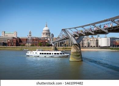 City of London, United Kingdom 6th July 2019: Thames river cruise boat passing under bridge