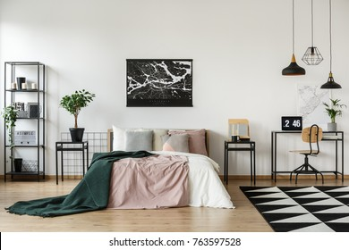 City map hanging on white wall above bed with pastel bedding and green coverlet in bright room with plants