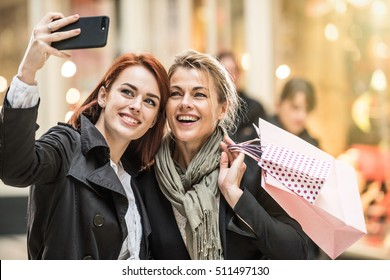 in the city, mother and daughter do shopping together, she takes the opportunity to make a selfie with a smartphone, lights of the shops at the background