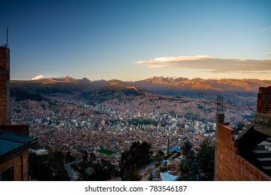 City and mountain sunset view of La Paz, the city in Bolivia. A viewpoint mirador at the 16 de Julio Mi Teleférico station. Cable cars and houses among the mountains ranges.