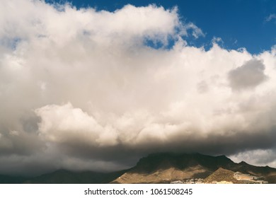 City in mountains with deep rainy clouds. Tenerife. Top view