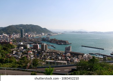 City near ocean in Fukuoka, Japan with blue sea and mountain, transportation across sea by  general cargo ship