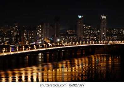 city at night and bridge with lights reflected in water of river