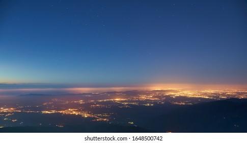 City at night illuminated with a star sky
