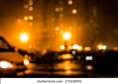 City night lights, moving car on a background of the house in a fog. Defocused image, in yellow tones