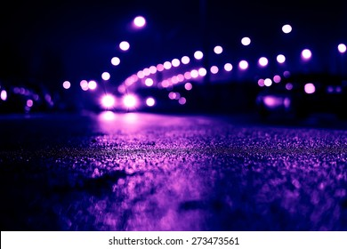 City night lights, road bridge with the lights and moving cars in the fog after rain. View from the level of asphalt, image in the purple-blue toning