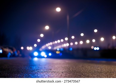 City night lights, road bridge with the lights and moving car in the fog after rain. View from the level of asphalt, in blue tones