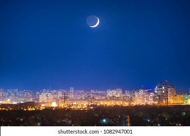 City at night with new moon on dark blue sky with stars