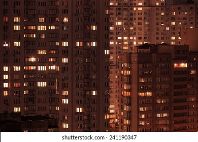City at night. Pattern of night city windows of modern residential building