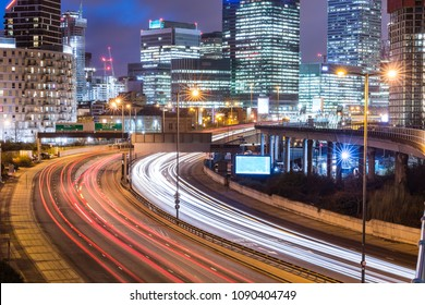 City night view with skyscrapers and traffic light trails. London urban scene in Canary Wharf with busy road and lights of financial district on background. Travel and architecture concepts