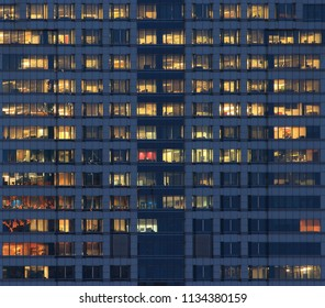 City office life. office workers light up the multiple floors office building and work overtime in the night time. glasses steel and aluminum clad modern office in Bangkok business district.
