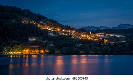 City on a mountain side in the evening when the lights reflect in the lake and the sky is filled with stars