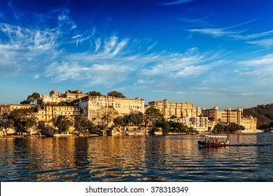 City Palace and tourist boat on lake Pichola on sunset. Udaipur, Rajasthan, India