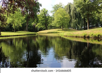 City park at the end of spring with fresh green colors, pond with trees such as the red and green beech trees around it. Photo was taken on a sunny day.