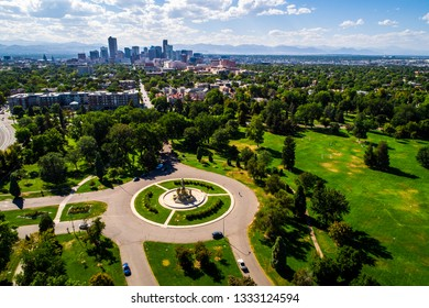 City park green spaces circle pattern monument aerial drone view high above Denver , Colorado Downtown skyline in background with Rocky Mountains sunny summer afternoon