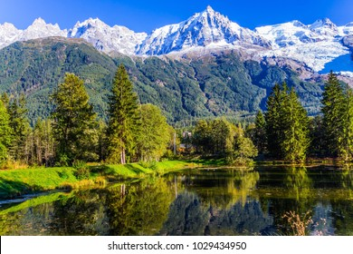 City - Park is illuminated by the sunset. The mountain resort of Chamonix - Mont Blanc. The lake reflected the evergreen spruce and snow-capped Alps. Concept of active and ecological tourism