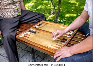 In the city park people play backgammon close up. The concept of leisure is the elderly.