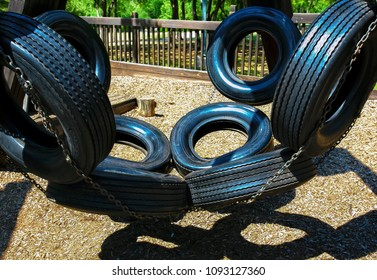 City park playground tire swing in the afternoonsummer sun, with tire shadows cast below them