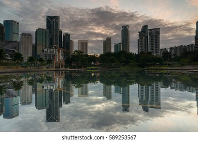 City park with a small forest island reflection and constructed high multi storey of offices near a city lake