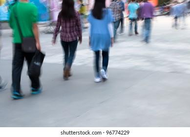 city people walking on street in motion blur