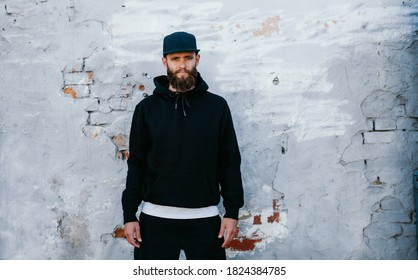 City portrait of handsome guy wearing black blank hoodie and baseball cap with space for your logo or design. Mockup for print