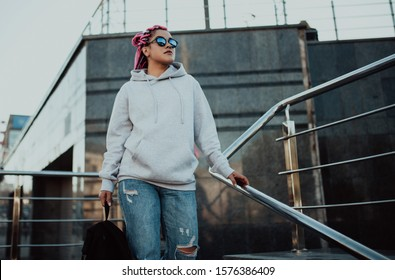 City portrait of handsome hipster girl with colored afro braids wearing gray blank hoodie or hoody with space for your logo or design. Mockup for print