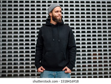City portrait of handsome hipster guy with beard wearing black blank hoodie or sweatshirt and hat with space for your logo or design. Mockup for print
