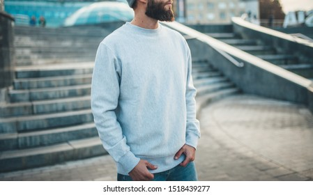 City portrait of handsome hipster guy with beard wearing gray blank hoodie or hoody and hat with space for your logo or design. Mockup for print