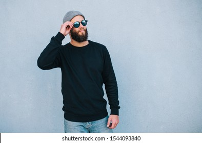 City portrait of handsome hipster guy with beard wearing black blank hoody or sweatshirt and hat with space for your logo or design. Mockup for print