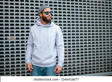 City portrait of handsome hipster guy with beard wearing gray blank hoodie or sweatshirt with space for your logo or design. Mockup for print
